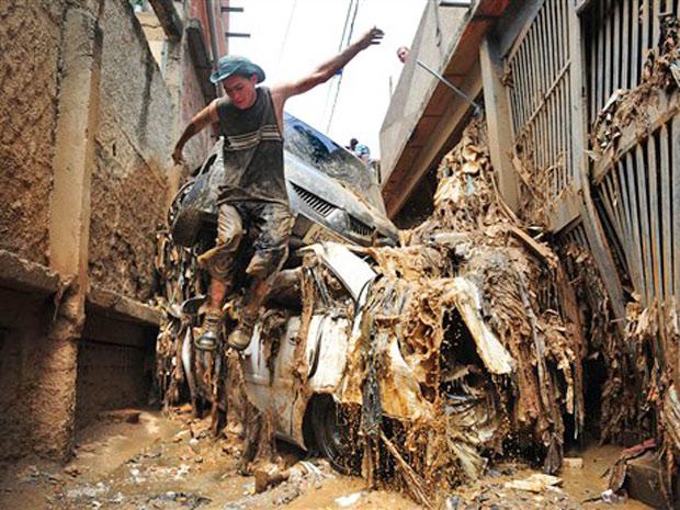 Homem pula escombros após fortes chuvas em Caracas