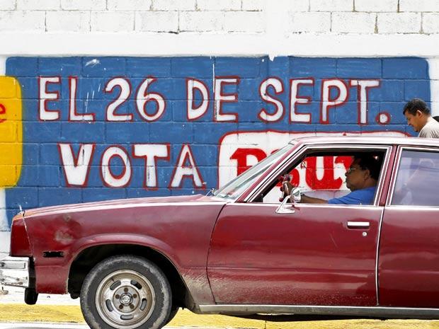 Carro passa perto de propaganda partidária para incentivar o voto em Caracas