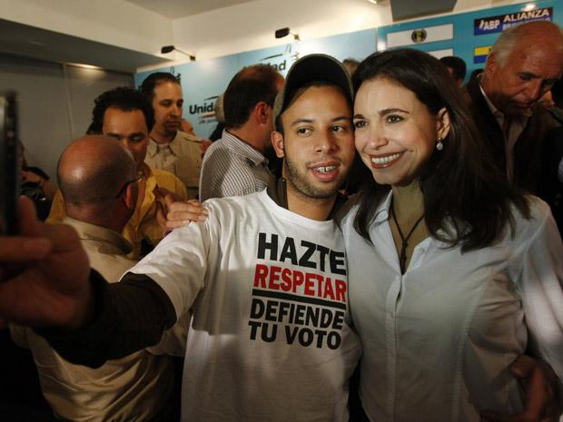 Eleita, a candidata oposicionista Maria Corina posa para fotos com eleitores.