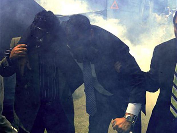 Usando máscara de gás, Correa deixa o regimento em Quito nesta quinta (30).