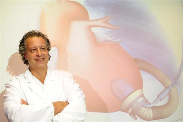Cirurgia cardíaco posa ao lado de esquema explicativo do implante permanente de coração artificial