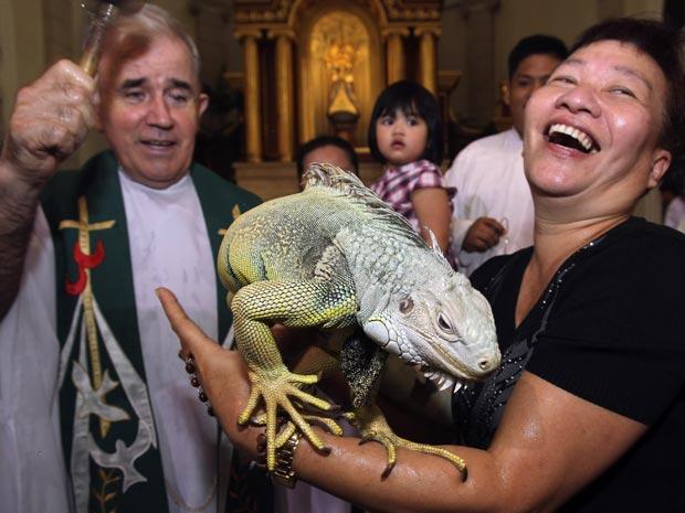 Ming Sandig leva seu iguana para abençoar por um padre católico neste domingo (3) na tradicional bênção dos animais na igreja de Malate, em Manila, capital das Filipinas.