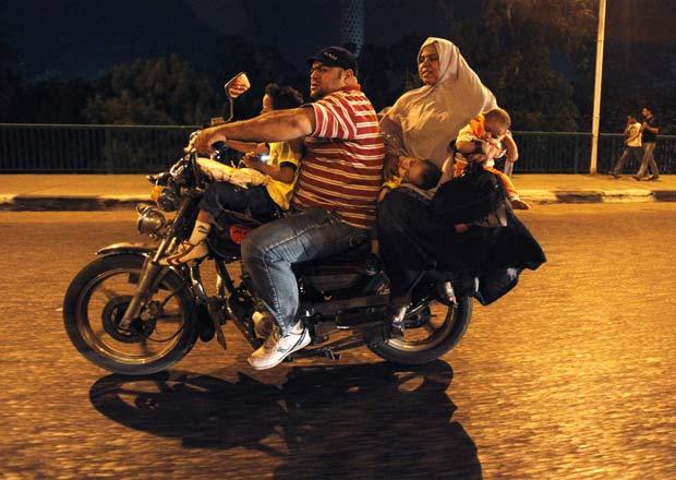 Um motociclista foi flagrado no domingo na cidade do Cairo, no Egito, carregando cinco pessoas em uma moto, incluindo dois bebês. A cena de imprudência foi registrada pelo fotógrafo Asmaa Waguih.