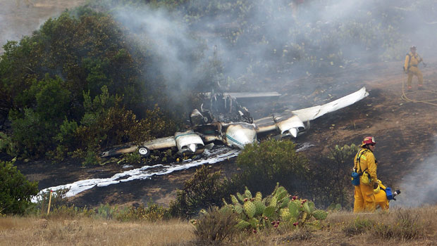 Bombeiros trabalham nos destroços de avião Cessna 310 que caiu próximo ao aeroporto da ilha de Santa Catalina, na costa sul da Califórnia, no final da tarde deste domingo (3). Três pessoas ficaram feridas com queimaduras.