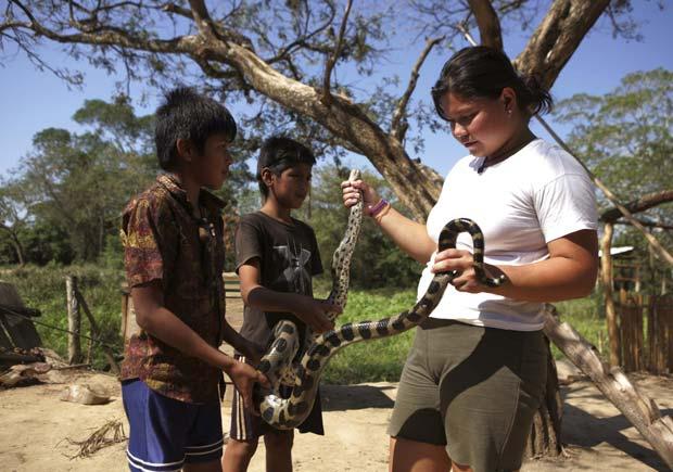 Karen Salvatierra e seus irmãos seguram cobra mantida como animal de estimação.