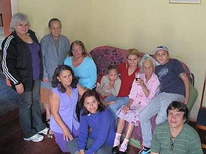 Antonia, com uma taça de vinho na mão, e parte da família reunida.