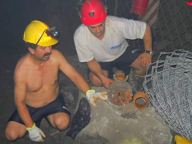Os mineiros Juan Illanes Palma (à esquerda) e Mario Gomez exibem peça usada em perfuradora que trabalha no resgate deles