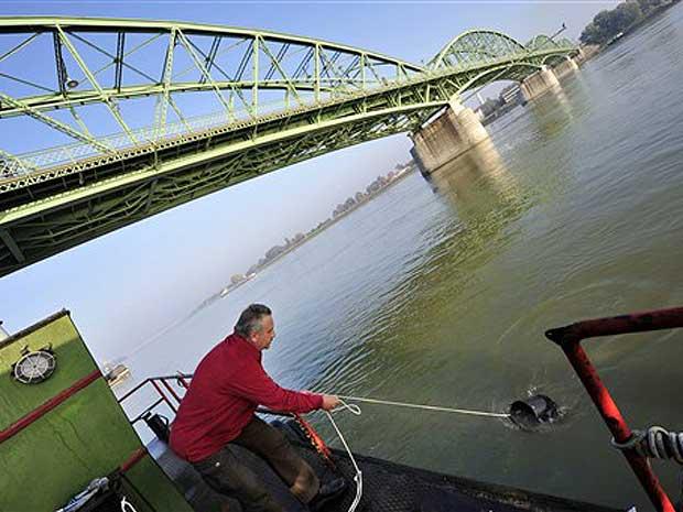 Funcionário do serviço ambiental da Hungria coleta água para testes no Rio Danúbio em Komarom, a de 110 km de Budapeste.