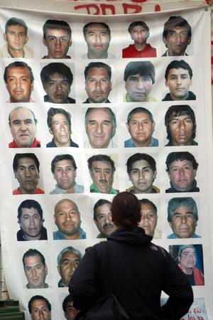 Jornalista observa painel com as fotos dos 33 mineiros presos, nesta sexta-feira (8), na Mina San José.