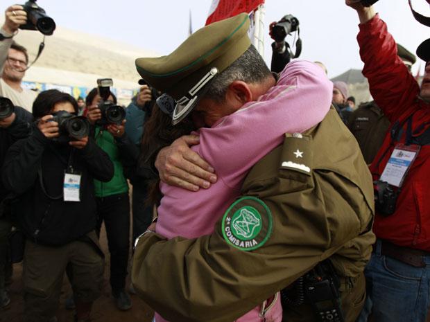 Parente de mineiro preso abraça policial neste sábado (9) na mina San José.