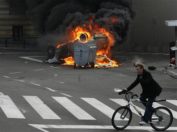 Ciclista passa por carro incendiado durante confrontos em Belgrado neste domingo (12).