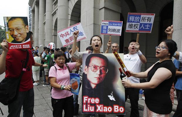 Manifestantes pró-democracia mostram cartazes com foto do Nobel da Paz Liu Xiaobo em Hong Kong neste domingo (10).
