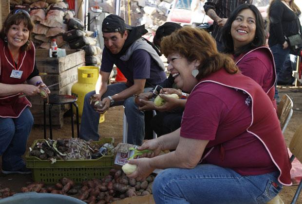 Voluntárias preparam refeição no acampamento nesta segunda-feira (11).