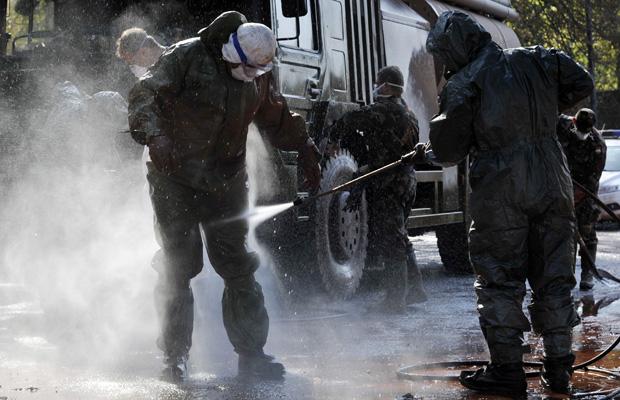 Militares limpam-se depois de mais um dia desintoxicando a região afetada, nesta segunda-feira (11), na Hungria.