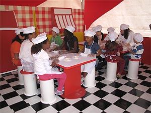 Crianças preparam mini-hot dogs na minicozinha
