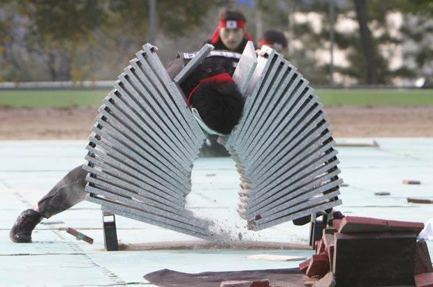 Policial quebra blocos de concreto durante treinamento.