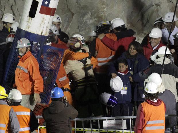 Florencio Ávalos, o primeiro mineiro resgatado, chega à superfície; no centro, seu filho, Byron, de 7 anos, chora.