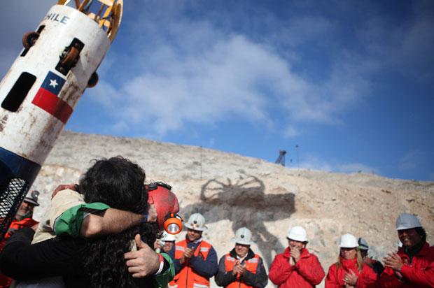 O mineiro chileno Alex Vega abraça sua esposa (à esq.) após ser resgatado da mina San Jose