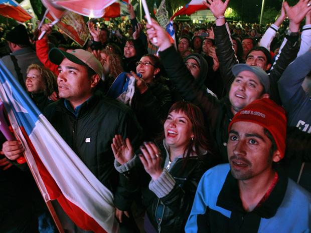 Moradores de Copiacó celebram a subida de Mario Sepúlveda à superfície, na madrugada desta quarta-feira (13).