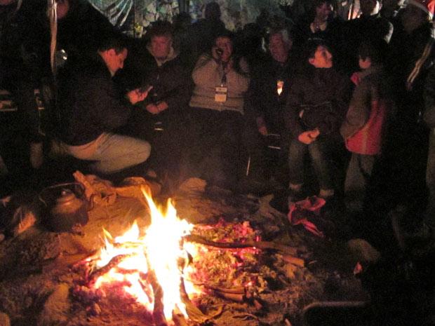 Familiares aquecem-se em torno de fogueira no acampamento na madrugada desta quarta (12).