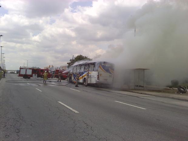 Bombeiros trabalham para conter o fogo no veículo.