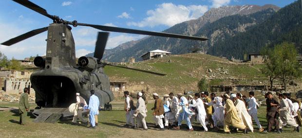 Refugiados paquistaneses, desalojados por causa das enchentes, correm para embarcar em helicóptero das Forças Armadas dos EUA