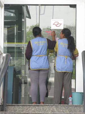 Funcionárias limpam restos de cartazes de greve em agência do Banco do Brasil na avenida Paulista.