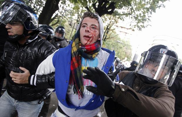 Estudante ferido é levado por policiais durante protesto em Lyon nesta segunda-feira (18).