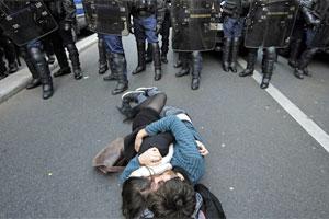 Casal beija-se na rua diante de bloqueio policial durante protesto em Paris, no dia 21