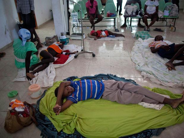 Haitianos infectados recebem tratamento contra cólera no chão da sala de espera de hospital em Grande-Saline