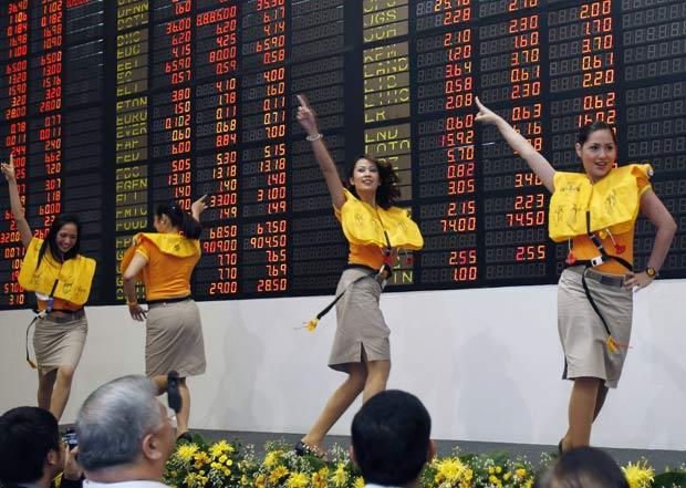 Aeromoças dançam na estreia da empresa na bolsa de valores de Filipinas.