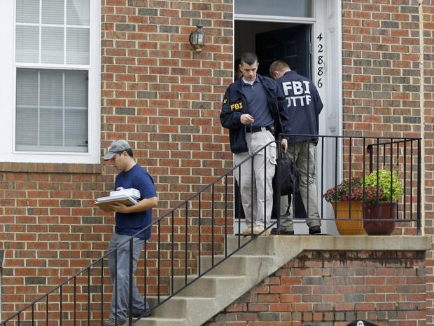 Investigadores do FBI deixam a casa de Farooque Ahmed em Ashburn, no estado americano da Virgínia, nesta quarta-feira (27).