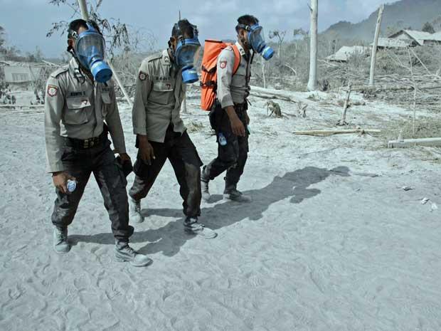 Policiais usam máscaras para investigar povoado atingido por nuvem de cinzas do vulcão Merapi em Kinahrejo, na Indonésia.