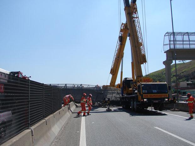 Operários trabalham na retirada de passarela da pista