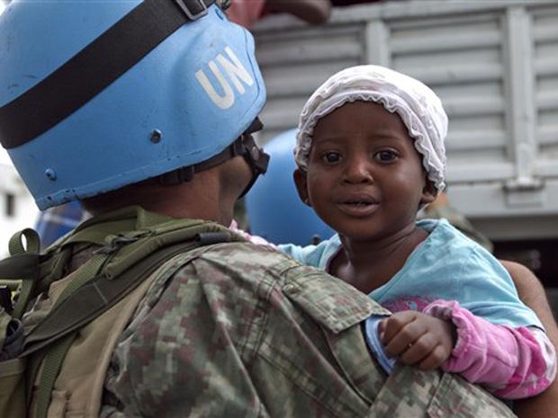 Soldado das forças de paz da ONU segura bebê durante trabalho de realocação de desabrigados nesta sexta-feira (5) em Porto Príncipe.