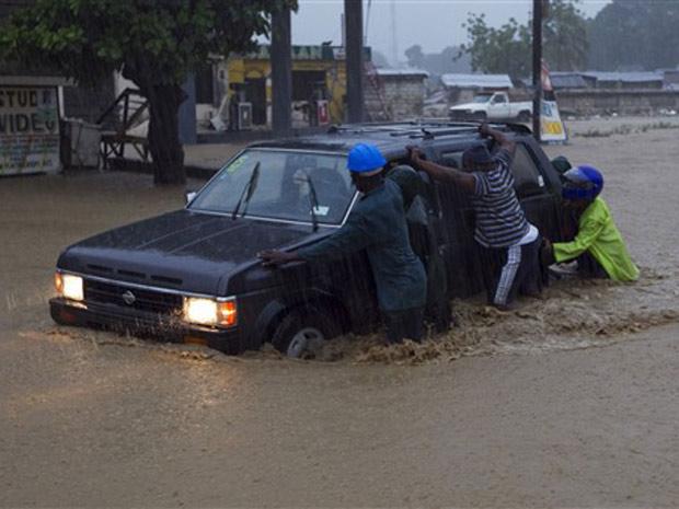 Moradores de Leogane empurram carro parado durante enchente nesta sexta-feira (5).