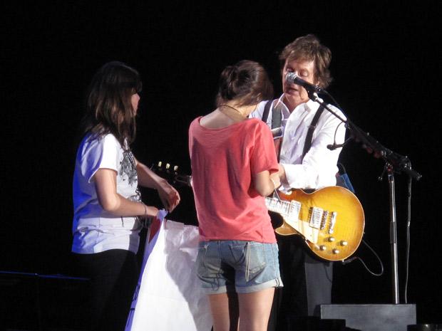 Paul no momento em que autografa o braço da menina Elisa. Ela havia escrito um cartaz explicando que vai imortalizar o 'presente' do ex-beatle cobrindo seu nome com uma tatuagem.