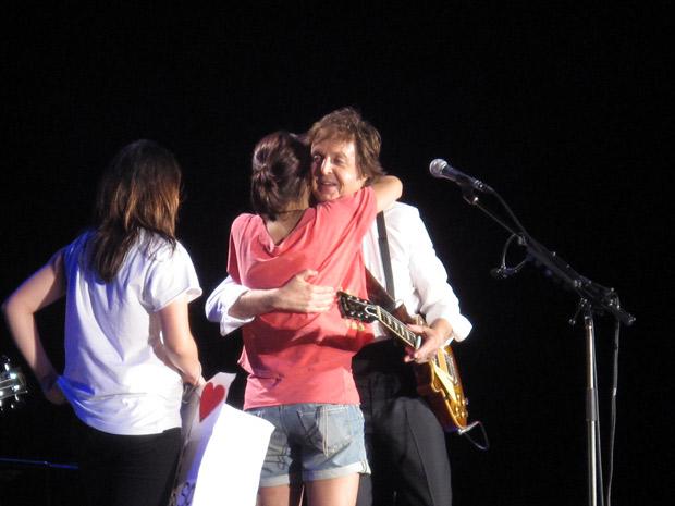 Fã ganha o abraço de Paul antes de deixar o palco. Apresentação contou com 36 músicas e durou três horas