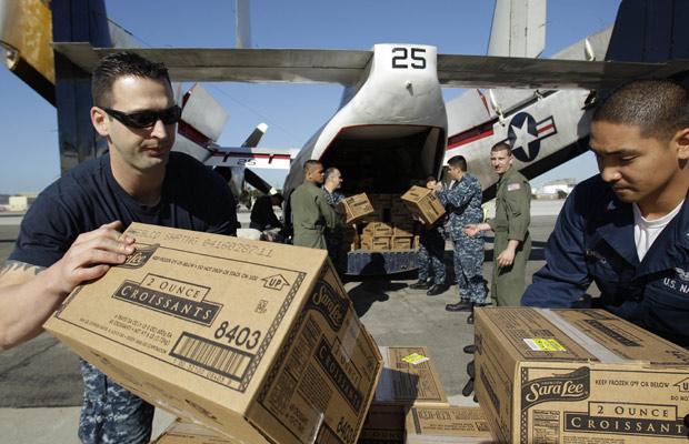 Marinheiros carregam caixas de croissants em avião para levar aos 4.500 à deriva no cruzeiro Carnival Splendor nesta terça-feira (9).