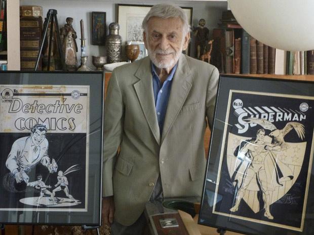 Jerry Robinson posa entre originais raros de HQs de Batman e do Super-Homem