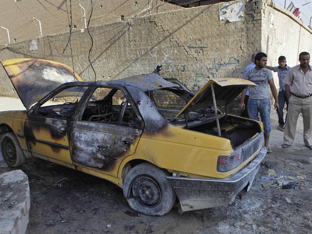 Pessoas observam local onde explodiu um carro-bomba, em Bagdá, nesta quarta