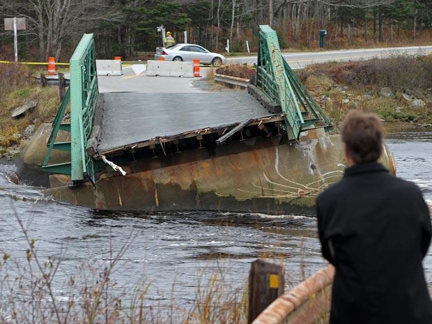 Morador observa ponte destruída pela força da correnteza do rio Tusket, na localidade de mesmo nome em Nova Escócia, Canadá, vêm sendo atingida por fortes chuvas