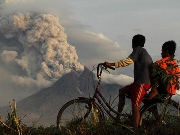 Crianças de bicicleta observam vulcão Merapi em atividade, na Indonésia