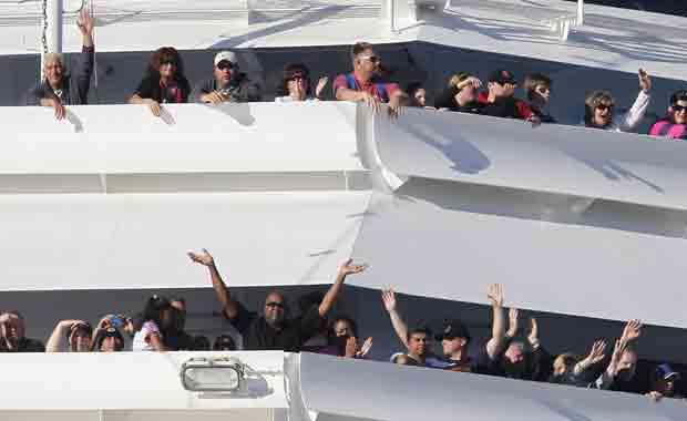 Passageiros acenam à medida que o Carnival Splendor se aproxima do porto de San Diego, na Califórnia, nesta quinta-feira (11).