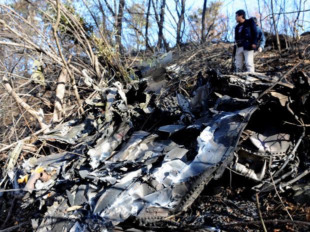 Soldado observa destroços de avião de reconhecimento RF-4C que caiu nesta sexta-feira (12) em Imsil, na Coreia do Norte.