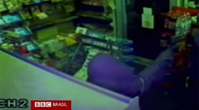 Imagem de câmera de segurança flagra momento em que assaltante aponta arma para criança.