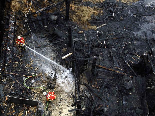 Bombeiros fazem rescaldo em viveiro no zoológico de Karlsruhe, na Alemanha, neste sábado (13). O fogo, ocorrido durante a madrugada, matou 26 animais, segundo a imprensa local.