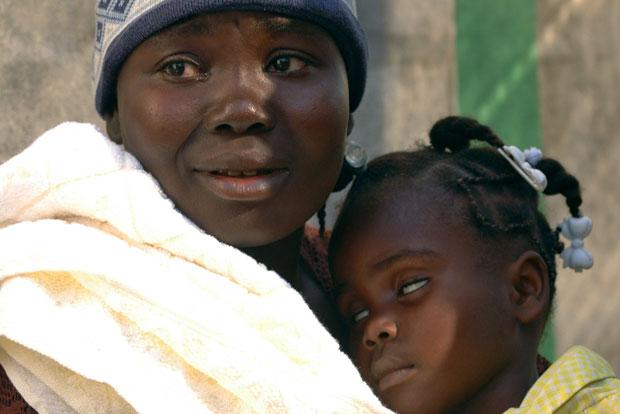 Haitiana ampara sua filha, com cólera, no Hospital Saint Catherine, na favela Cite-Soleil