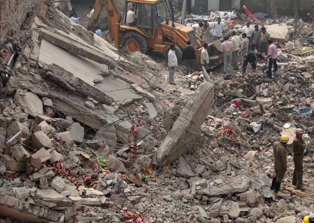 Equipes prosseguiam nesta quarta-feira (17) a remoção de destroços em prédio que caiu em Nova Délhi, capital da Índia, dois dias antes.
