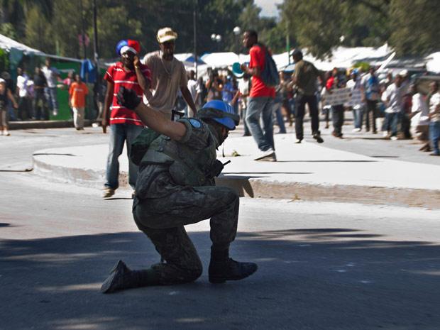 Um dos soldados da missão de paz brasileira cai de um caminhão em frente a manifestantes durante protesto em Porto Príncipe